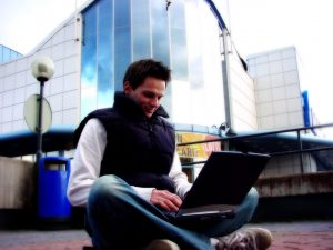 guy-with-laptop-social-media-posts-Charlotte-Monroe-Mooresville-Criminal-Defense-Lawyer-300x225